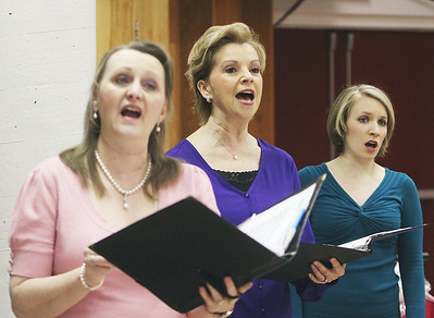 Chorus members Alice H. Johnson, Barbara Dowling and Kim Lamoureux, warm up before the performance.