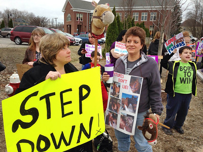 Protesters hoping Chair of the Board of Selectmen Cathy Richardson will resign following allegations of neglecting three horses taken from her farm, wait outside Dracut Town Hall before the meeting. From left, Debbie Martin, Sandra Perry, and Matthew Miller, 7, all of Dracut. (SUN/Julia Malakie)